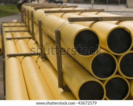 A pile of yellow and black plastic construction pipes strapped together. Toronto, Ontario, Canada. - stock photo