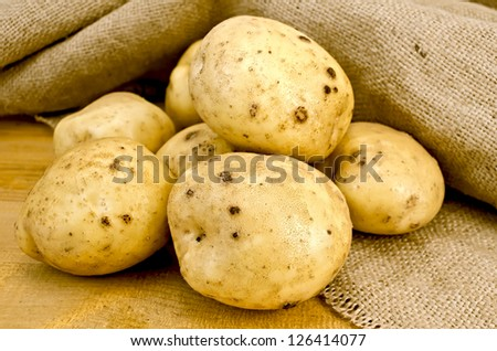 A pile of yellow potato tubers against sacking and wooden board - stock photo