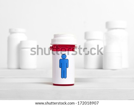 A pill bottle with a male figure on the label sits in the foreground of other bottles. - stock photo