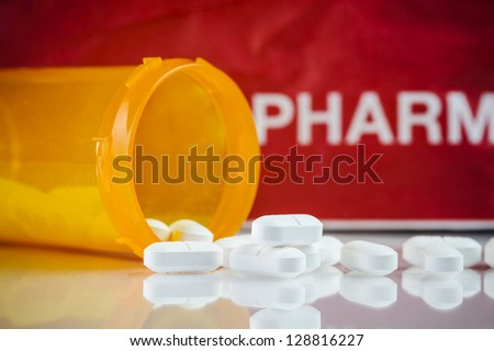 a pill bottle with prescription pills and pharmacy paper bag in the background - stock photo
