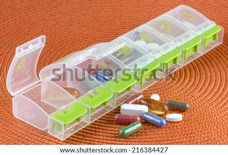 a pill box with a weeks supply of pills - stock photo
