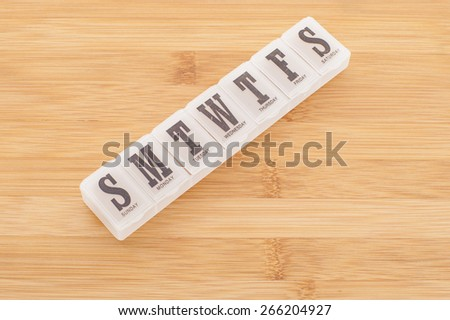 A pill dispenser box for one week usage contains separate containment for daily dosage medication. - stock photo