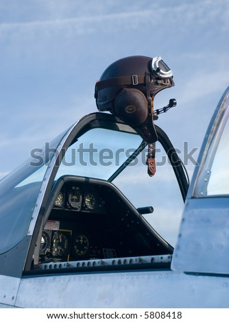 A pilot's leather flying helmet atop a P-51 Mustang fighter plane - stock photo
