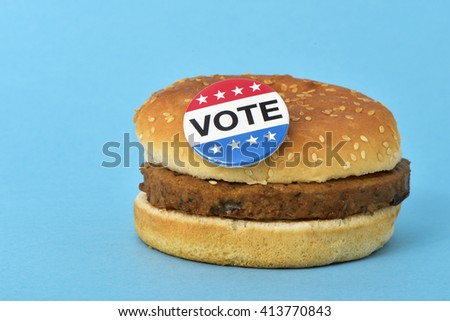 a pin button with the text vote for the the United States election on a hamburger, on a blue background - stock photo