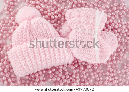A pink baby hat and booties for a girl, with a background of pink pearls, horizontal - stock photo