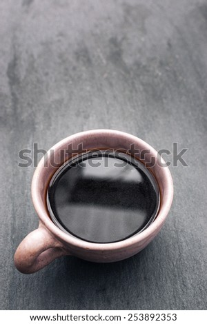 A Pink Coffee Cup Containing Freshly Brewed Black Coffee on a Slate Backround. With Copy Space. - stock photo