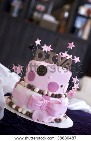 A pink fondant cake with Diva and stars topping it featured in a bakery.  Shallow DOF with focus on the front of the cake. - stock photo