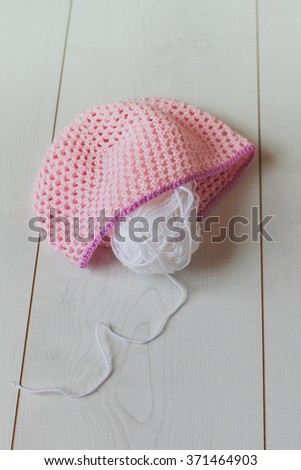 A pink knitted baby hat and a ball of white yarn on a white background - stock photo