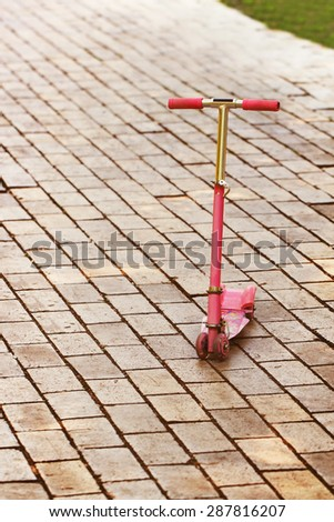 A pink skating scooter on the pavement road in the park - stock photo