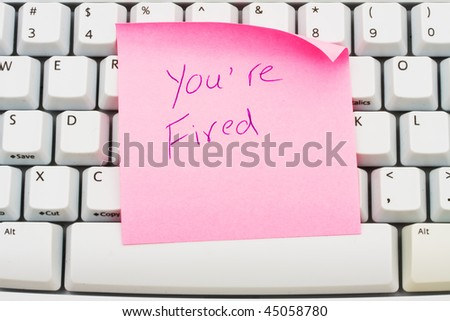 A pink sticky note sitting on a computer keyboard, You are fired - stock photo