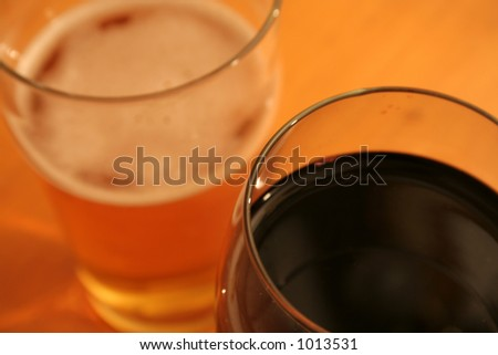 A pint of beer and a glass of red wine set against a wood grain table. - stock photo