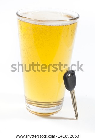 A pint of beer and a key to a vehicle isolated against a white background - stock photo