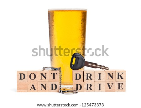 A pint of beer with a miniature pair of handcuffs and car key atop blocks spelling out Don't Drink and Drive isolated on a white background - stock photo