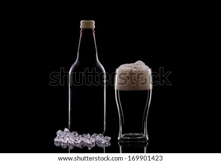 A Pint of Dark Beer and a Beer Bottle on a Black Background - stock photo