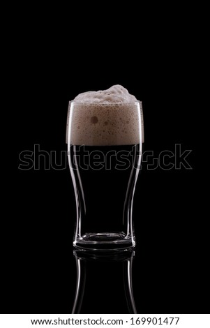 A Pint of Dark Beer on a Black Background - stock photo