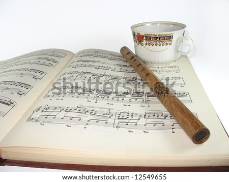 A pipe and a cup of coffe on musical notes - stock photo