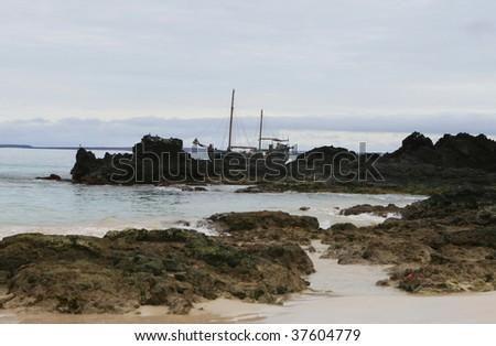 A pirate ship run aground on the rocky shoreline - stock photo