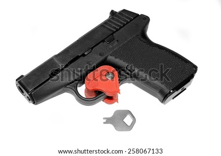A pistol that has the trigger locked with a key.  A firearm safety feature. - stock photo