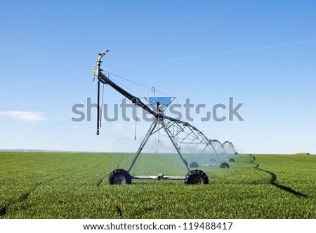 A pivot irrigation system watering a field of grain. - stock photo