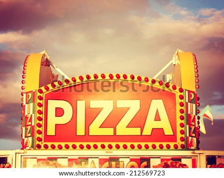 a pizza sign at the state fair on a hot sunny day right before dusk toned with a vintage retro instagram filter effect - stock photo