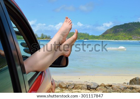 A place of a destination. Woman's legs dangling out a car window parked at the beach - stock photo