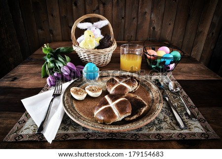 A place setting of Easter Breakfast of eggs and hot cross buns.  Processed in a lightly bleached rustic retro style.  - stock photo