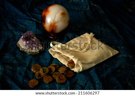 A plain muslin bag with wooden runes spilling out over a sparkling blue cloth with amethyst and crystal ball in the background. - stock photo