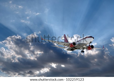a plane above Sun rays going through dark clouds - stock photo