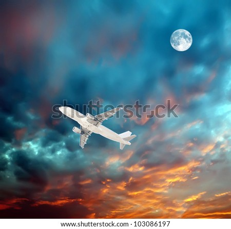 A plane flying high in the nighttime sky with an illuminated moon. - stock photo