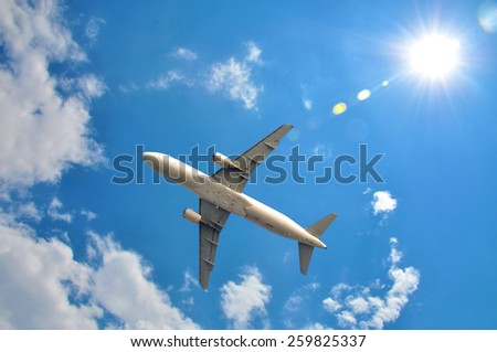 A plane is flying in the sky and sun  - stock photo