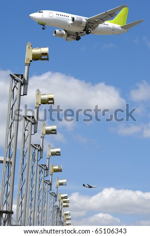 A plane is flying over landinglights in airport. - stock photo