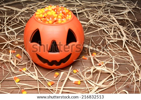 A plastic Halloween pumpkin filled with candy corn on a wood table scattered with straw.  - stock photo