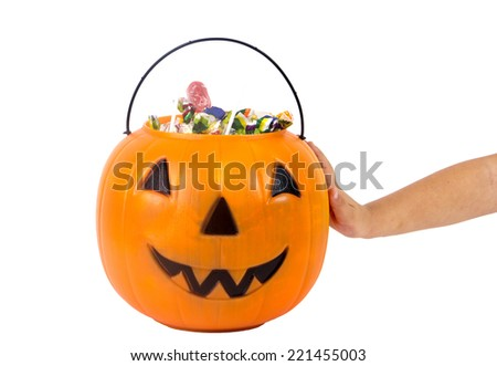 A plastic pumpkin filled with candy and hand of kid  - stock photo