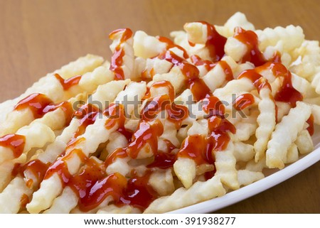 A plate full of delicious crinkle cut style french fries with ketchup - stock photo