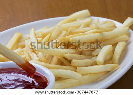 A plate full of delicious shoestring style french fries with ketchup - stock photo