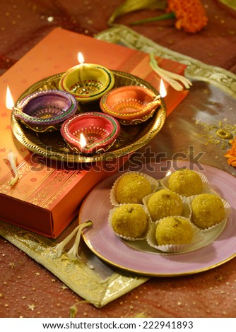 A plate full of Indian sweet, an illuminated oil lamps and a gift box- A biggest festival, Diwali still life. - stock photo