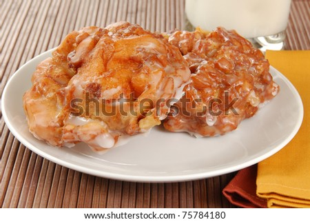 A plate of apple fritters and a glass of milk - stock photo