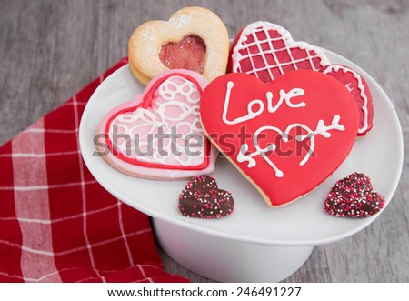 A plate of assorted Valentine's day cookies on a rustic table - stock photo