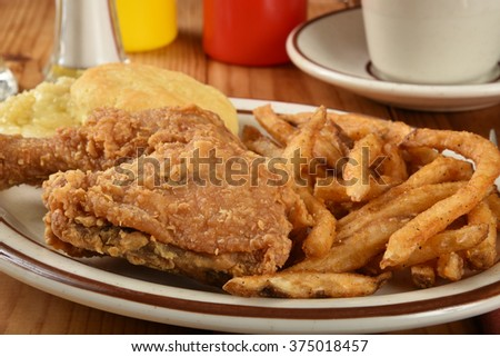 A plate of chicken and biscuits with french fries close up - stock photo