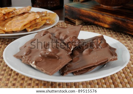 A plate of chocolate bark with almonds and of peanut brittle - stock photo