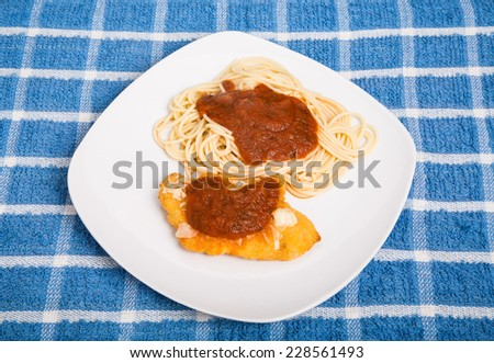 A plate of classic chicken parmesan on a blue plaid placemat - stock photo