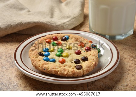 A plate of cookies with chocolate candy sprinkles and a glass of milk - stock photo