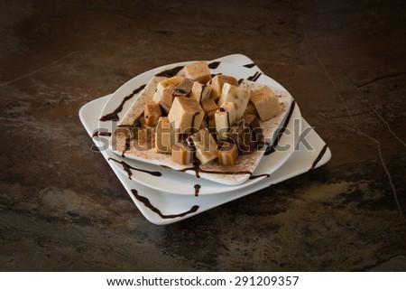 A plate of delicious, melt-in-your-mouth fudge. A little cocoa powder and chocolate syrup is lightly drizzled on top for the finishing touches. A nice photo for sugar, dessert, romantic or other ideas - stock photo