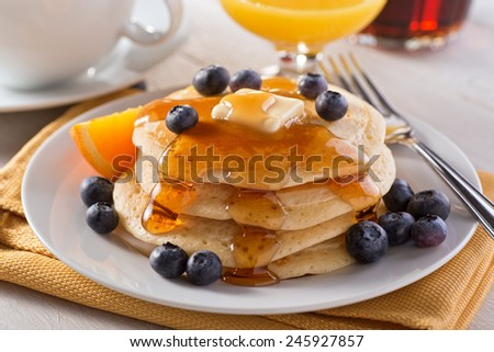 A plate of delicious pancakes with fresh blueberries and maple syrup. - stock photo