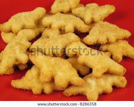 A plate of dinosaur-shaped chicken nuggets copes with extinction issues as they suffer the effects of deep frying. - stock photo