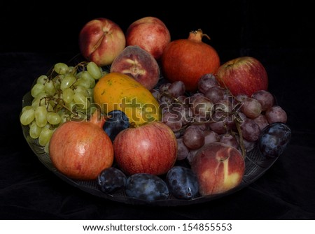 a plate of fruit on a black background - stock photo