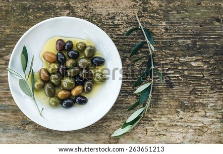 A plate of Mediterranean olives in oil with branch of olive tree. Top view, copy space - stock photo