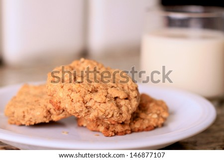 A plate of peanut butter oatmeal cookies served with a cold glass of milk. These cookies are completely vegan and the milk is almond milk. - stock photo