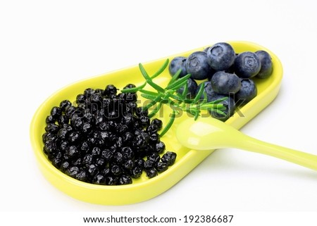 A plate of ripe blueberries and shriveled blueberries. - stock photo