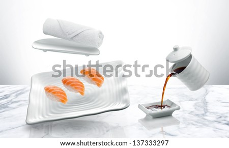 A plate of sushi, with soy sauce gravy boat flying over a marble table - stock photo